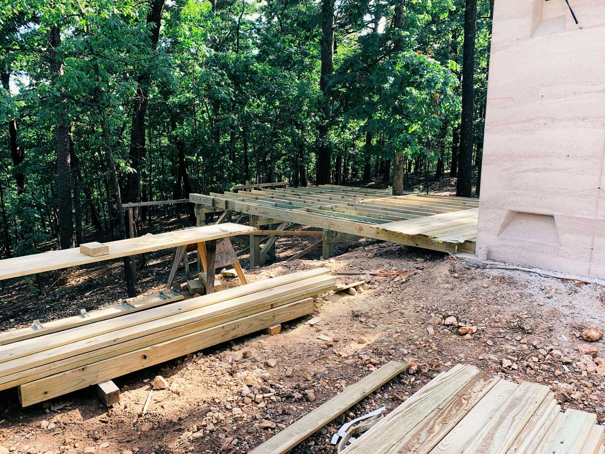 A modern wood deck under construction at the rammed earth house project in Eureka Springs, AR