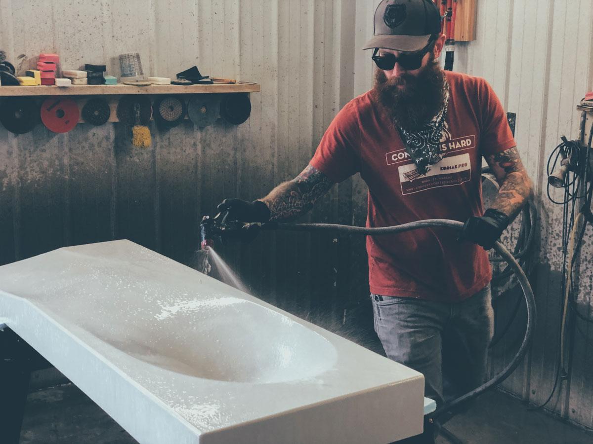 Brandon Gore processing a GFRC concrete sink in preparation of concrete sealer