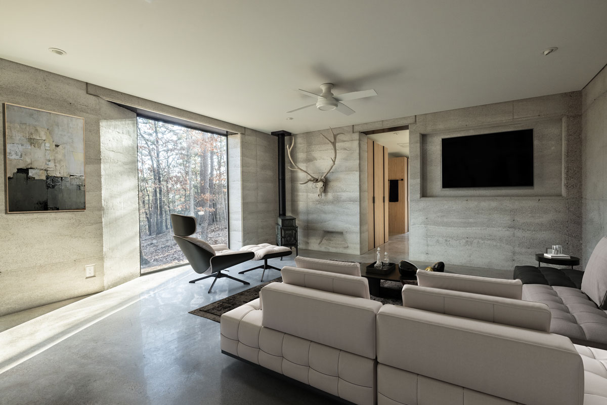 This modern living room could be on the cover of Dwell Magazine with the rammed earth walls, polished concrete floors, and massive steel and glass windows.