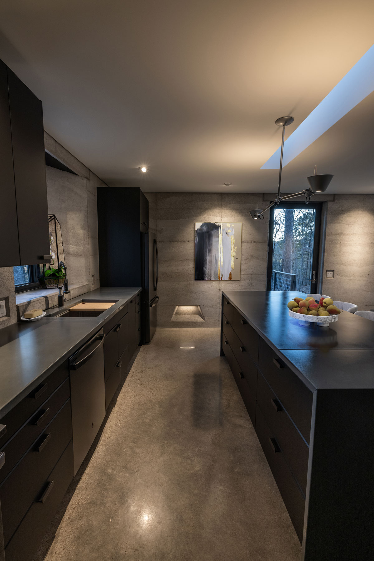 A modern kitchen in a rammed earth house featuring custom concrete countertops and matte black cabinets