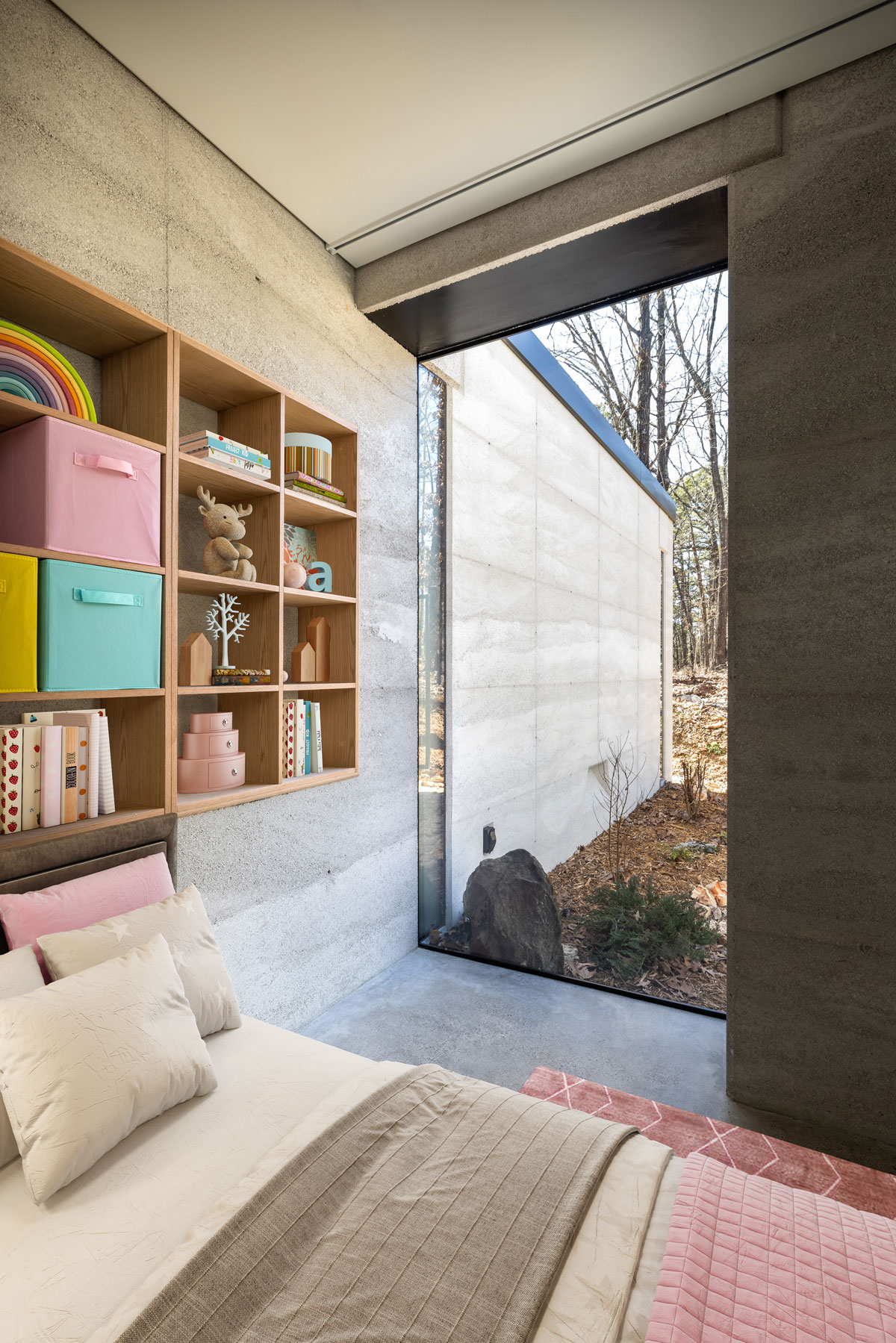 A large glass window blurs the line between interior and exterior spaces in this modern rammed earth cabin located in Eureka Springs, AR, USA