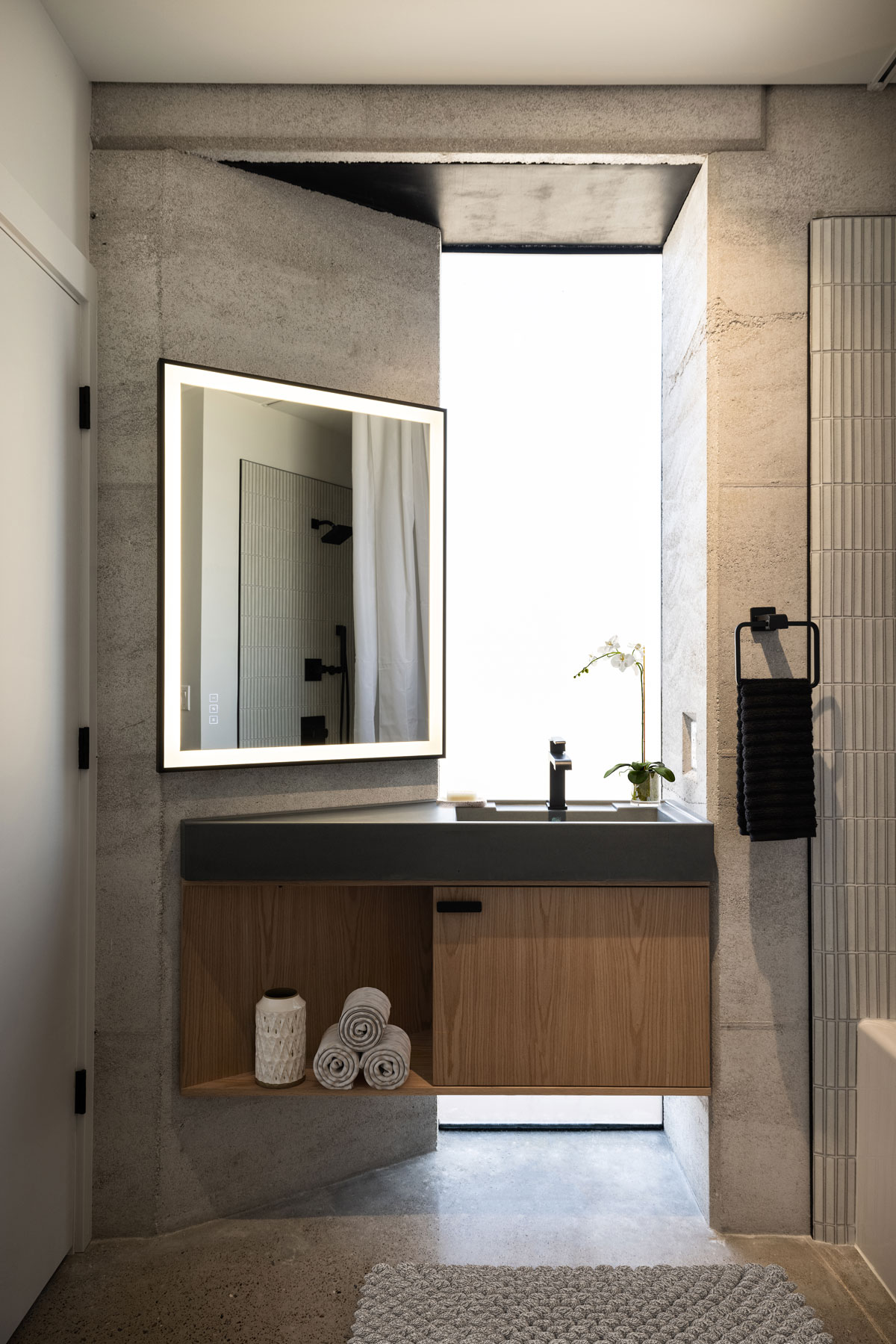 This floating custom concrete sink rests on a handcrafted modern oak cabinet in this rammed earth bathroom