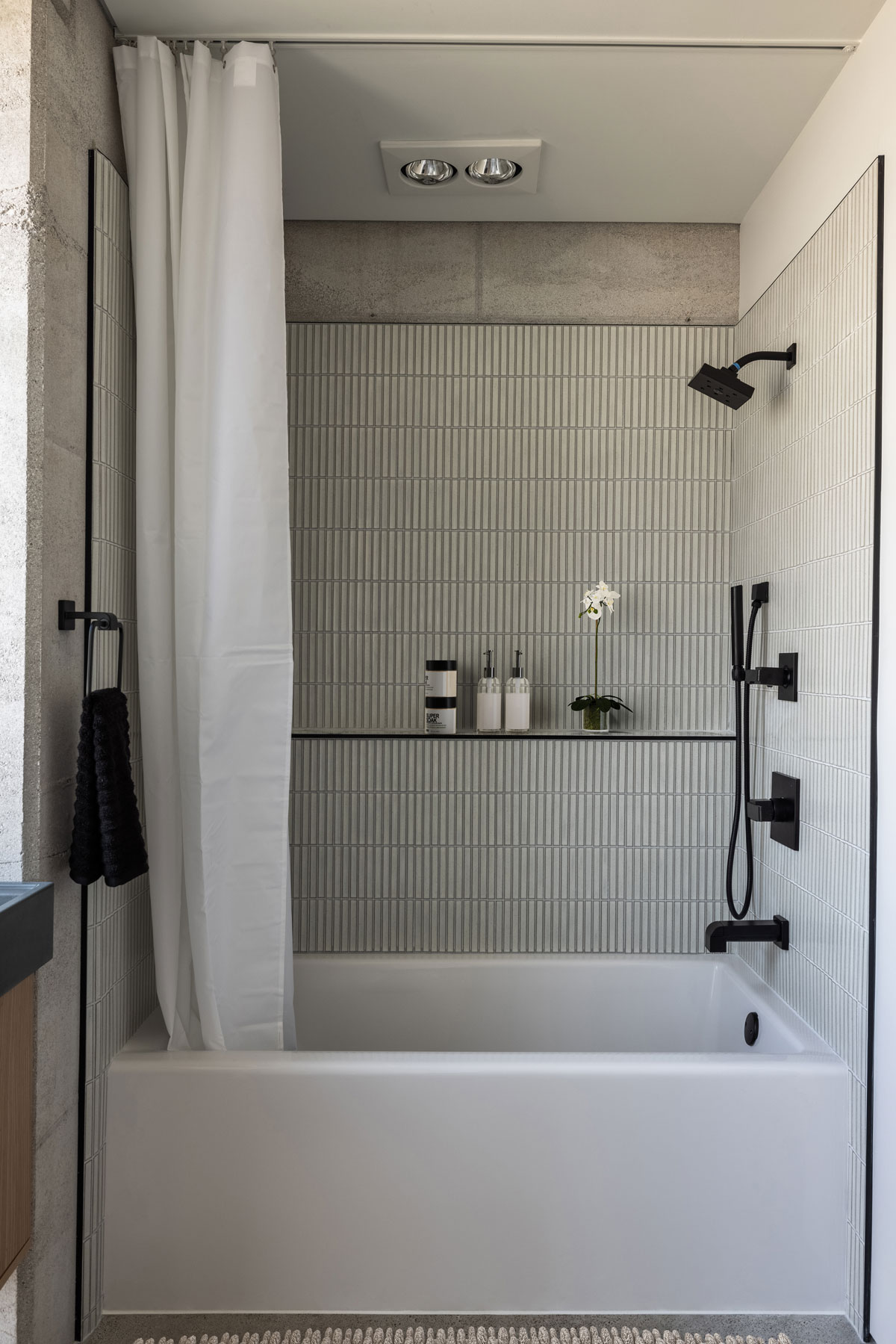 Japanese ceramic tile frame this simple tub in a rammed earth bathroom