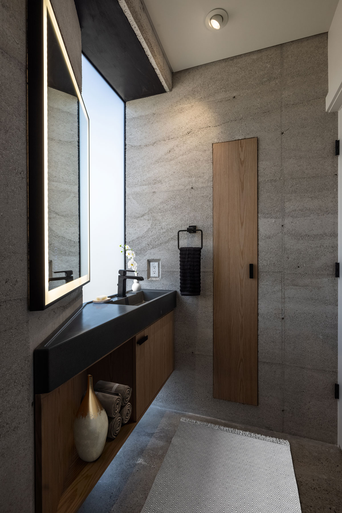 The powder bath in the modern CALX Cabin rammed earth house showcases this bespoke concrete sink and floating cabinet handcrafted in the USA by Hard Goods.