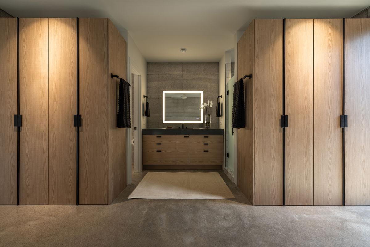 The bespoke oak wardrobes in the master bedroom frame the custom concrete sink set against a limestone rammed earth wall