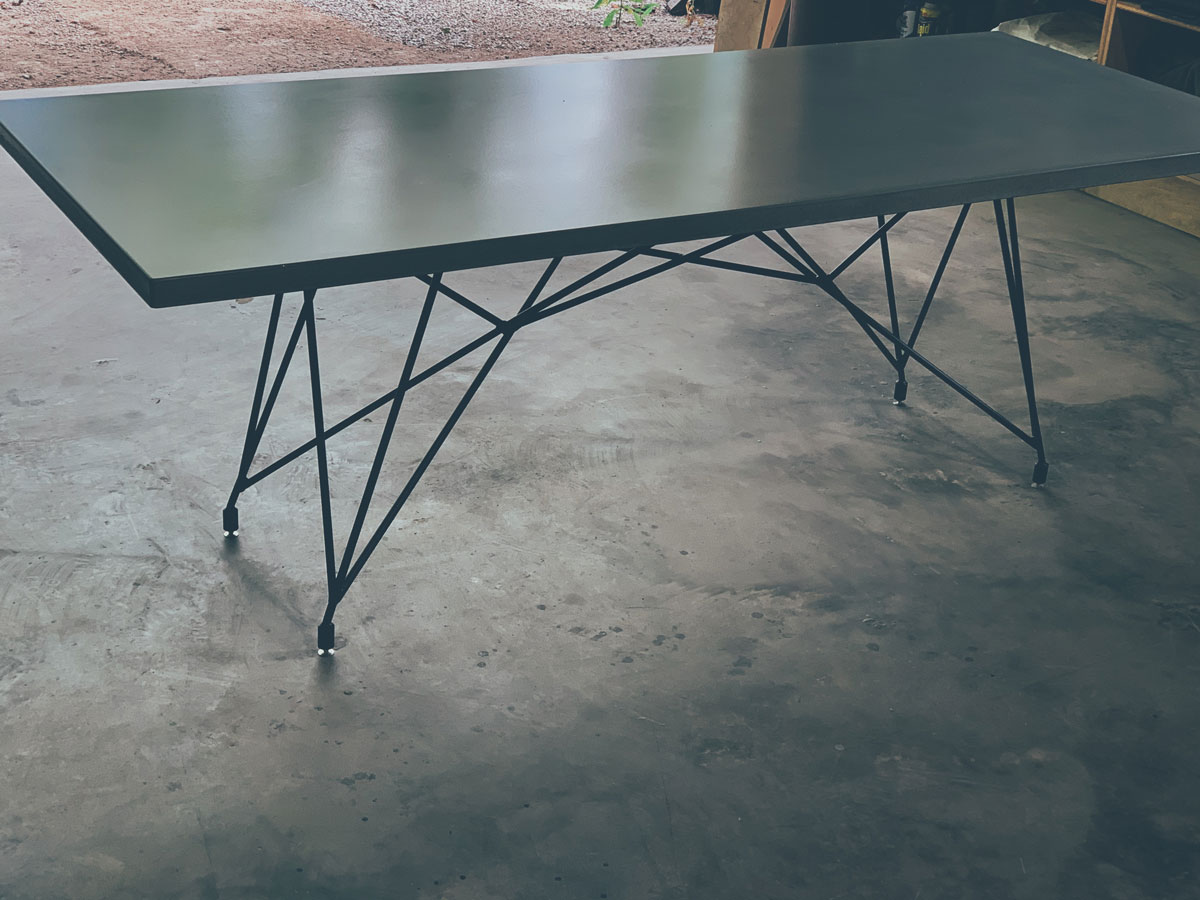 A mid century modern concrete and steel outdoor dining table, handmade in the Ozark Mountains of NW Arkansas