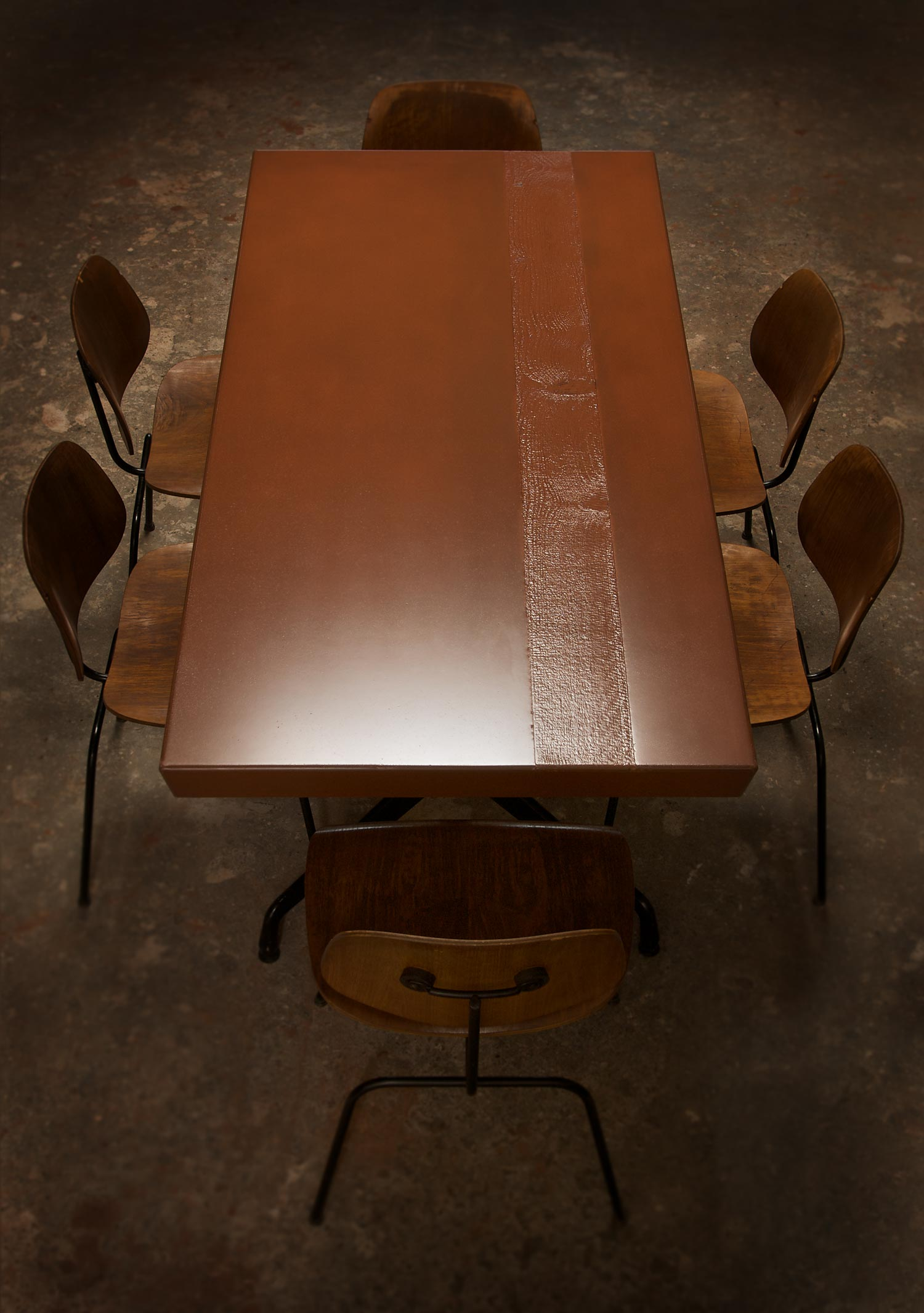 Handmade red concrete dining table with a wood texture inlay