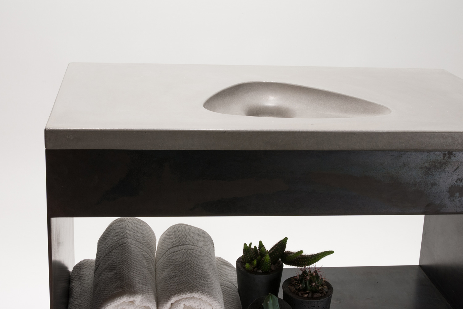 A simple, modern triangular concrete sink on a black steel sink base