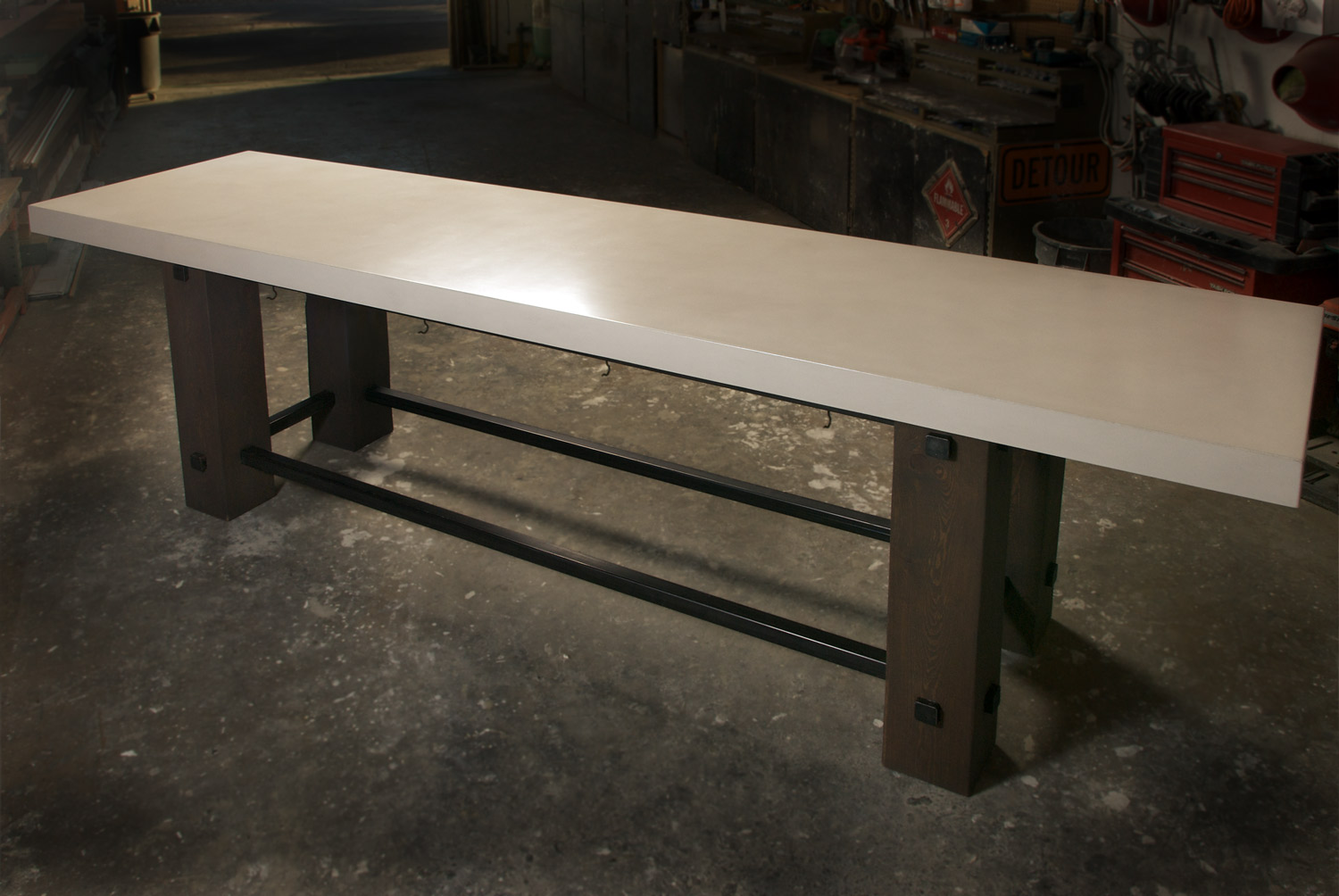 A large white concrete community dining table with a wood and steel base for a restaurant in Denver, CO