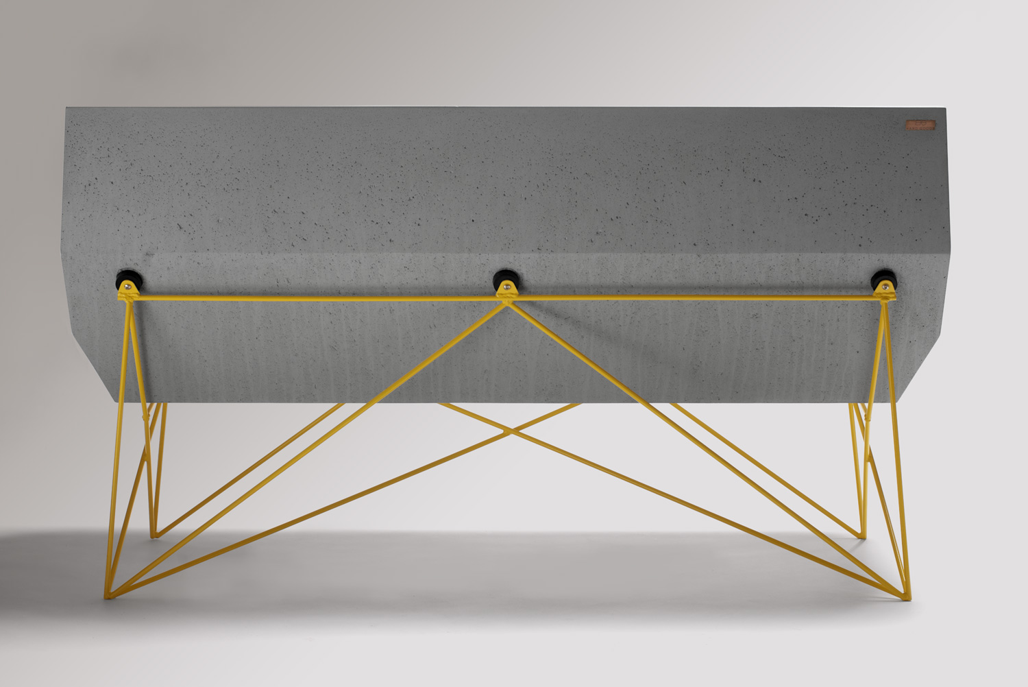 The back of a custom GFRC concrete MCM bench with a yellow steel rod base