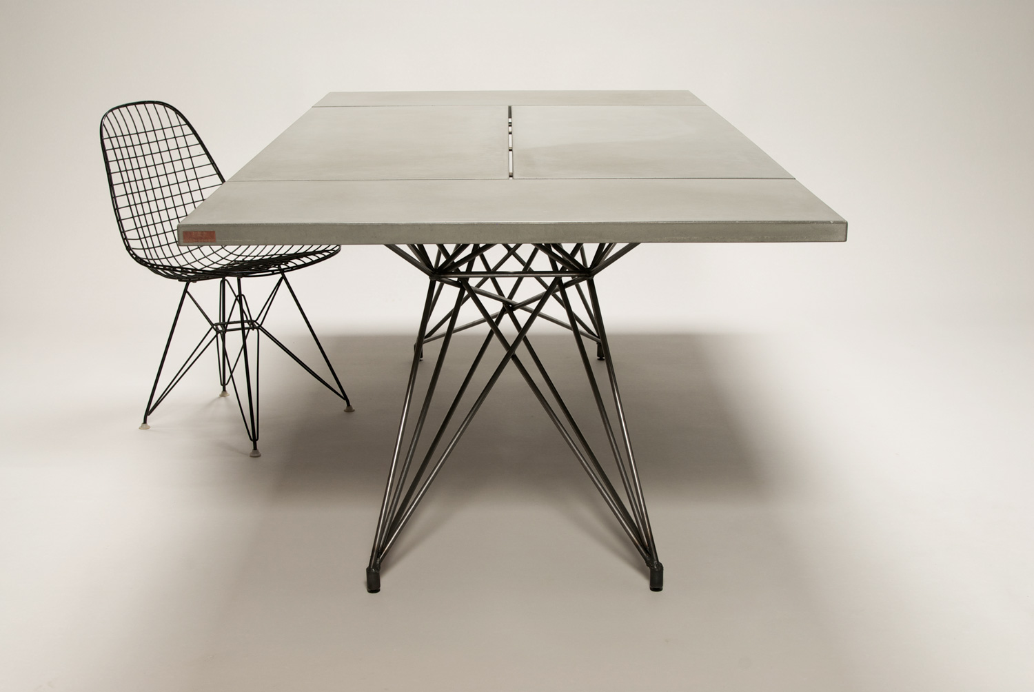 Custom concrete and steel modern dining table with an Eames wire dining chair