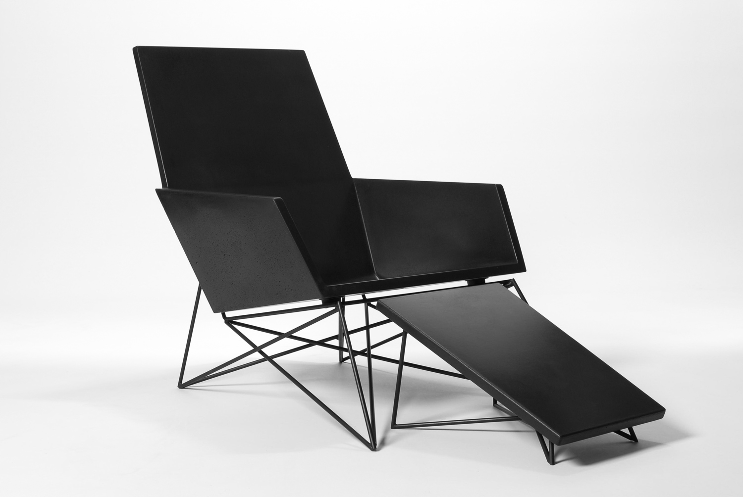 Modern black concrete outdoor chair with the optional concrete + steel ottoman