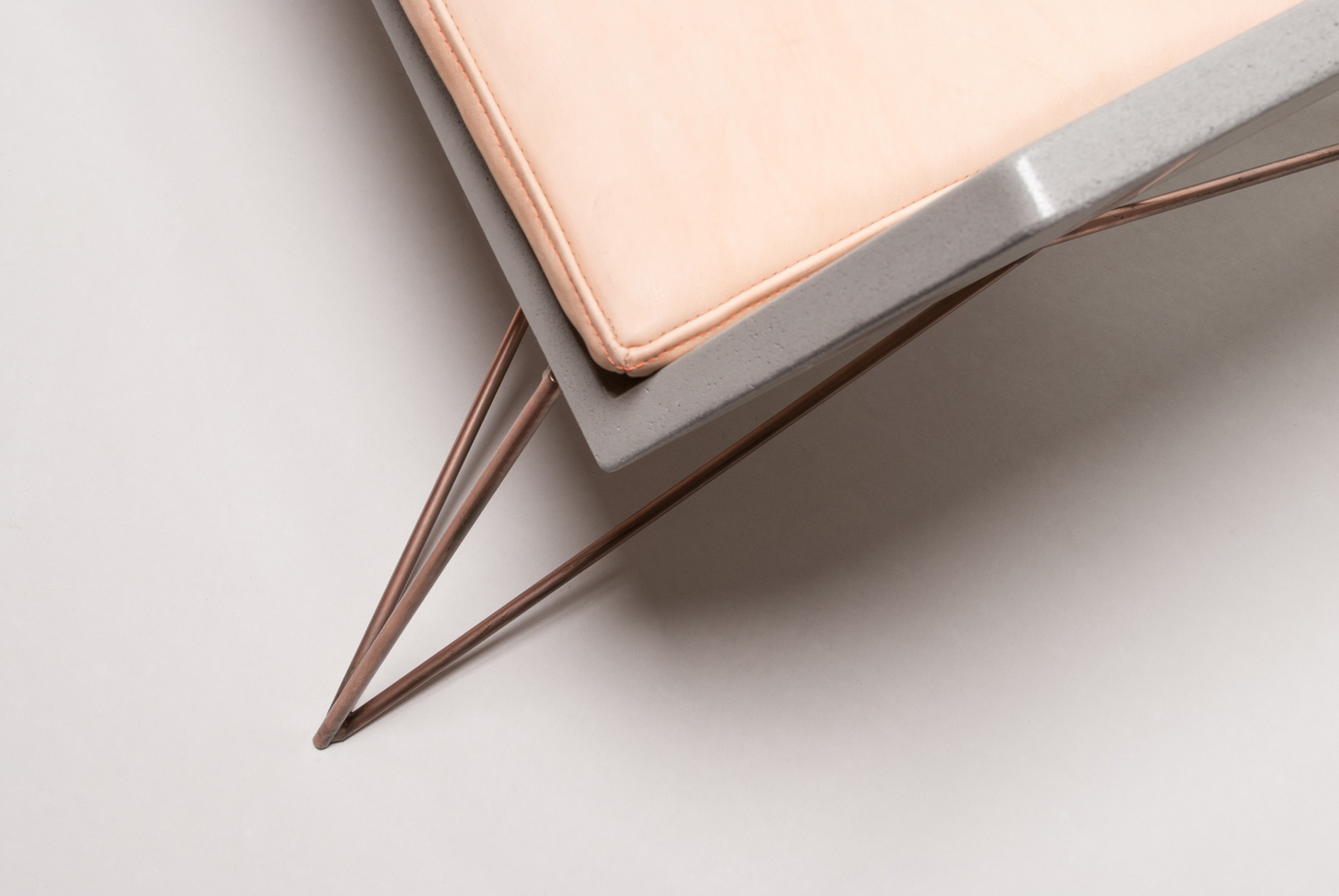 detail of the leather cushion on the concrete chair with the copper base