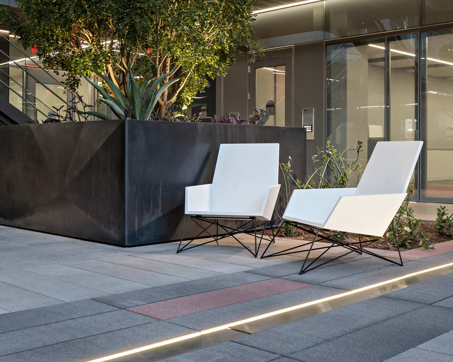 2 modern white outdoor concrete chairs next to black faceted GFRC wall cladding panels