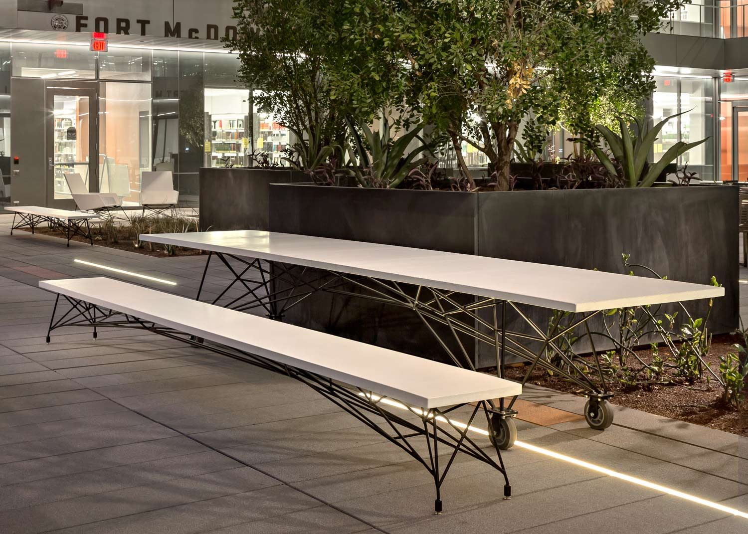 A custom white concrete communal table with a modern black steel base, and a custom concrete and steel bench. These pieces were made for a commercial project for ASU in Tempe, AZ