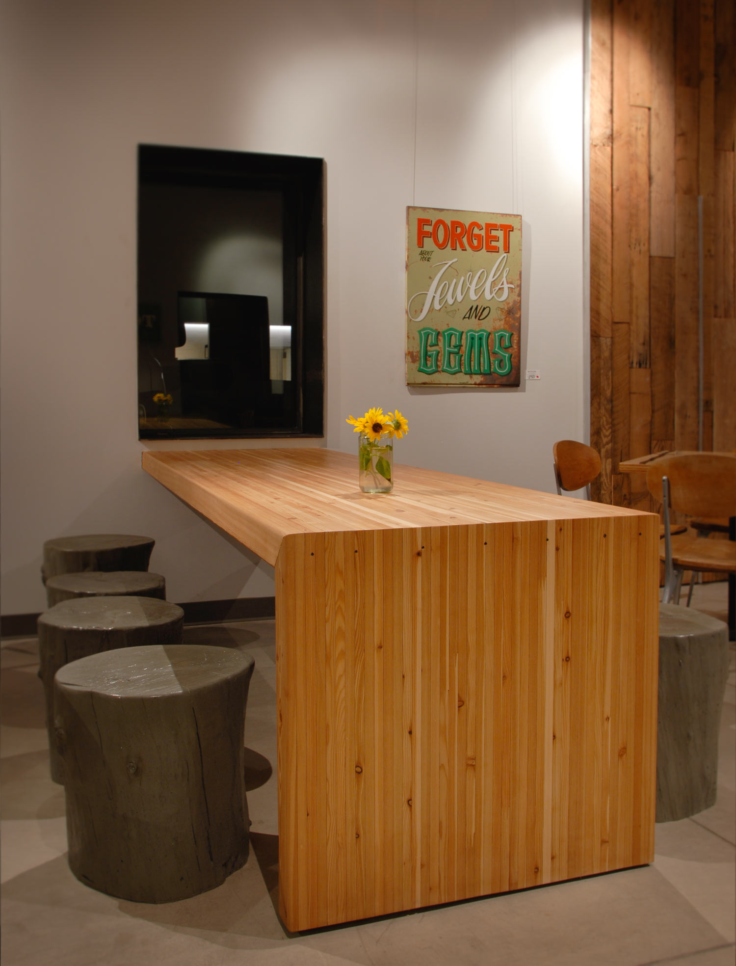 Several natural grey concrete tree stump stools around a community table at a restaurant in Phoenix, AZ