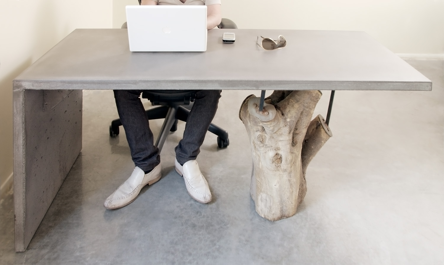 An artistic concrete desk with a tree stump leg supporting one end