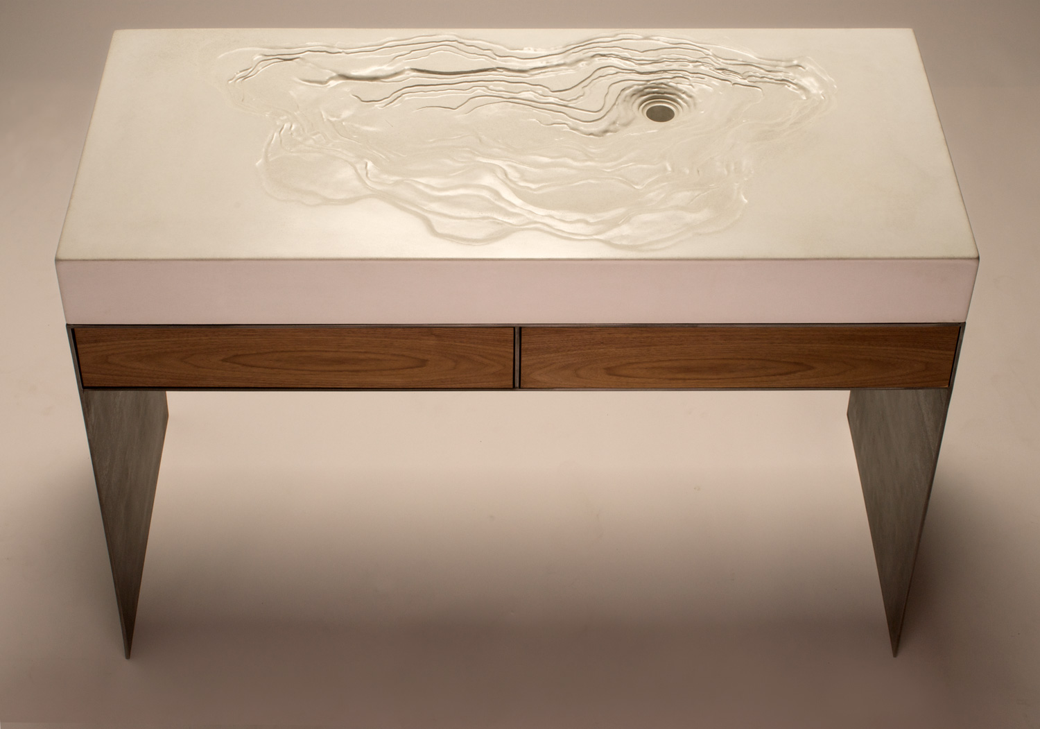 A white concrete ADA compliant Erosion Sink on a custom steel sink base with walnut drawers.