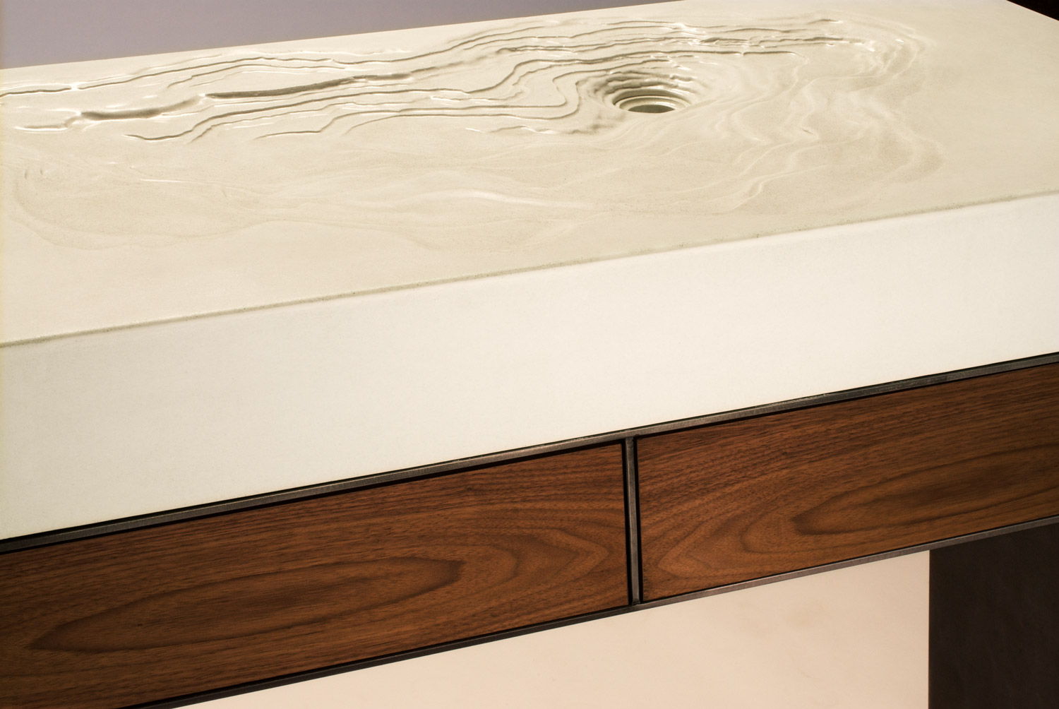 A concrete Erosion Sink on a custom steel base with walnut drawers featuring BLUM hardware. This sink was made for and exhibited at Dwell on Design in Los Angeles, CA