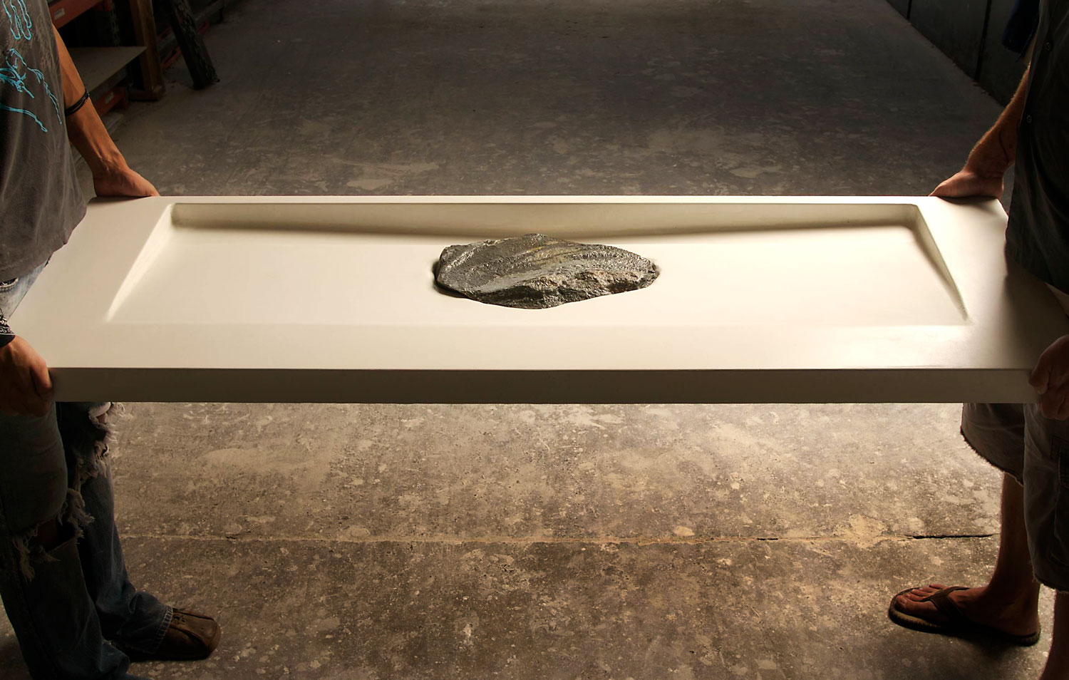 Custom white concrete double basin sink featuring an inlaid stone shelf in the center of the sink.