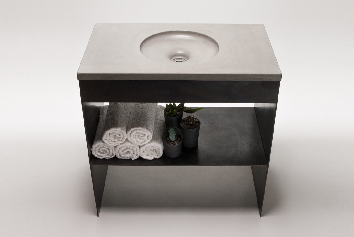 The Harrison Concrete Sink is a simple round concrete sink base, shown here on a black steel base