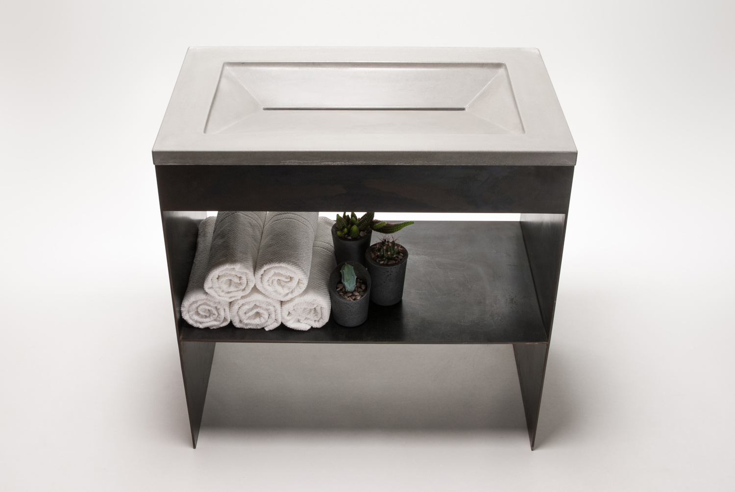 Concrete ramp sink, sometimes referred to as a wedge sink, on a custom steel sink base.