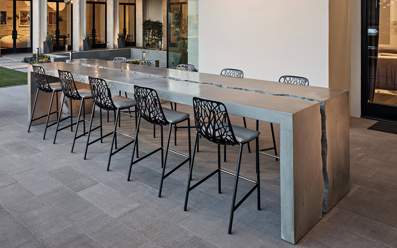 Large outdoor dining table, made of concrete, featuring a crack running through the center