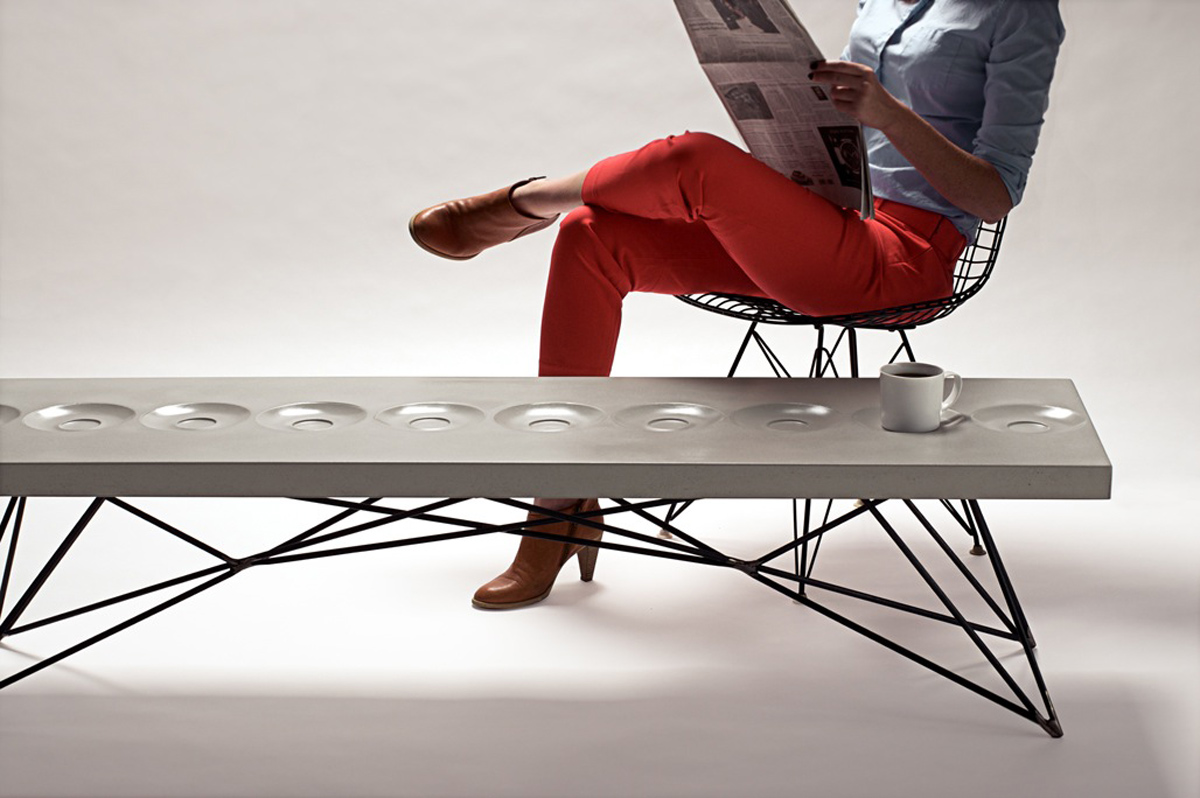 The Orson Concrete and Steel Coffee Table, featuring integral coffee saucers in the surface