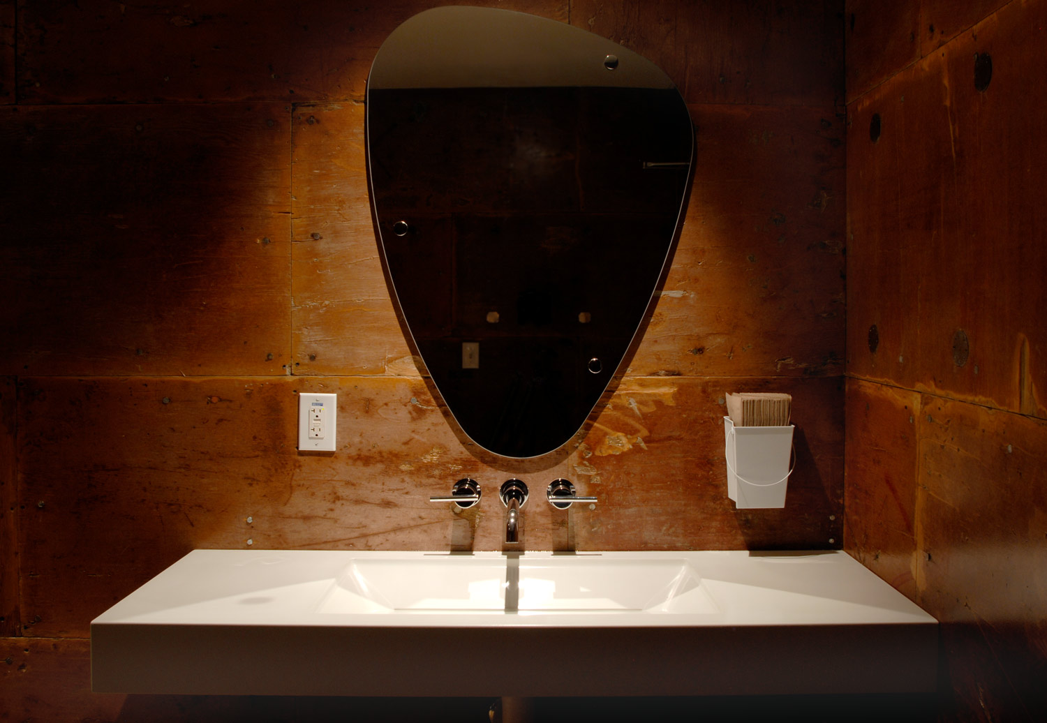 A modern white concrete sink in a rustic bathroom at a restaurant in Seattle, WA