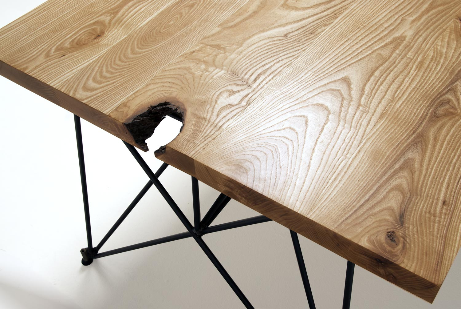 Detail of a modern wood dining table with a steel rod base, made in the USA