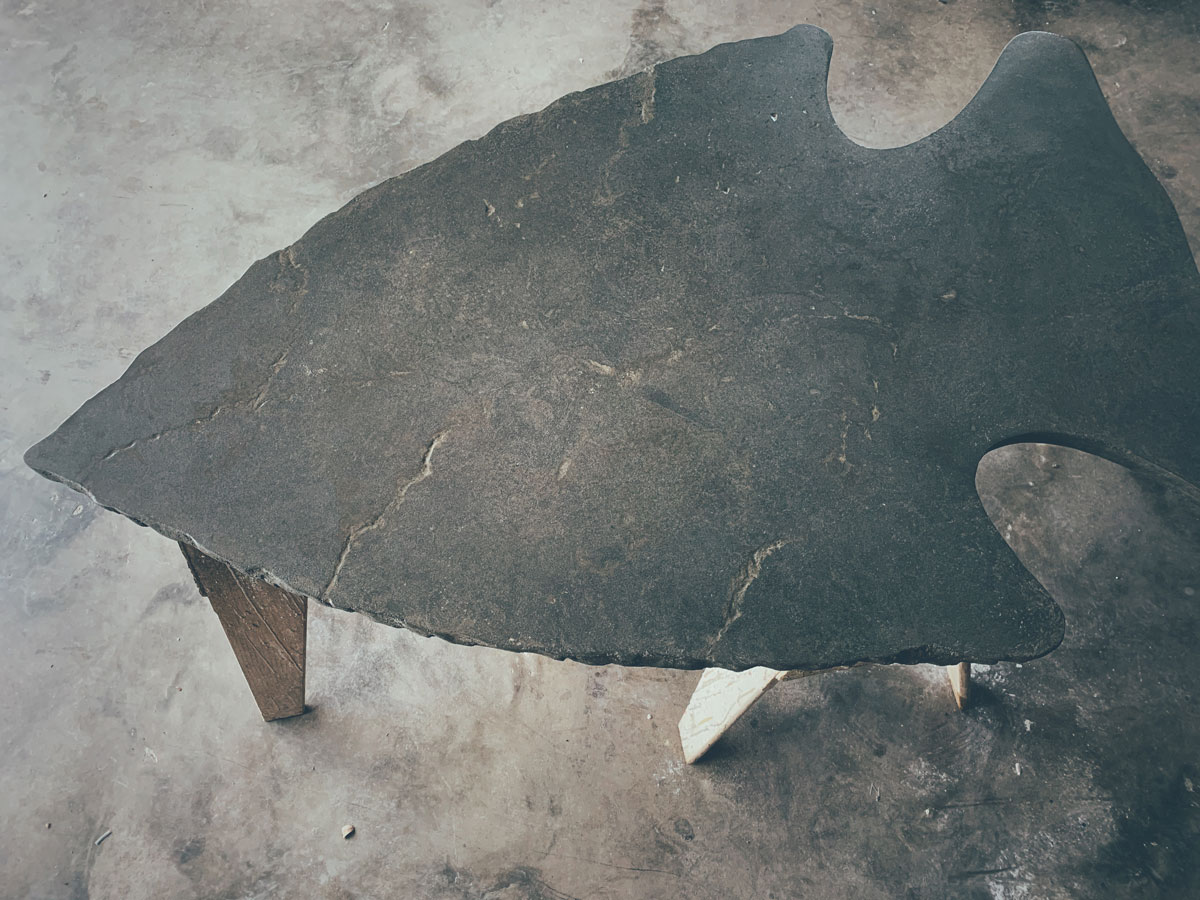 A concrete coffee table shaped like an arrowhead for a rustic lodge