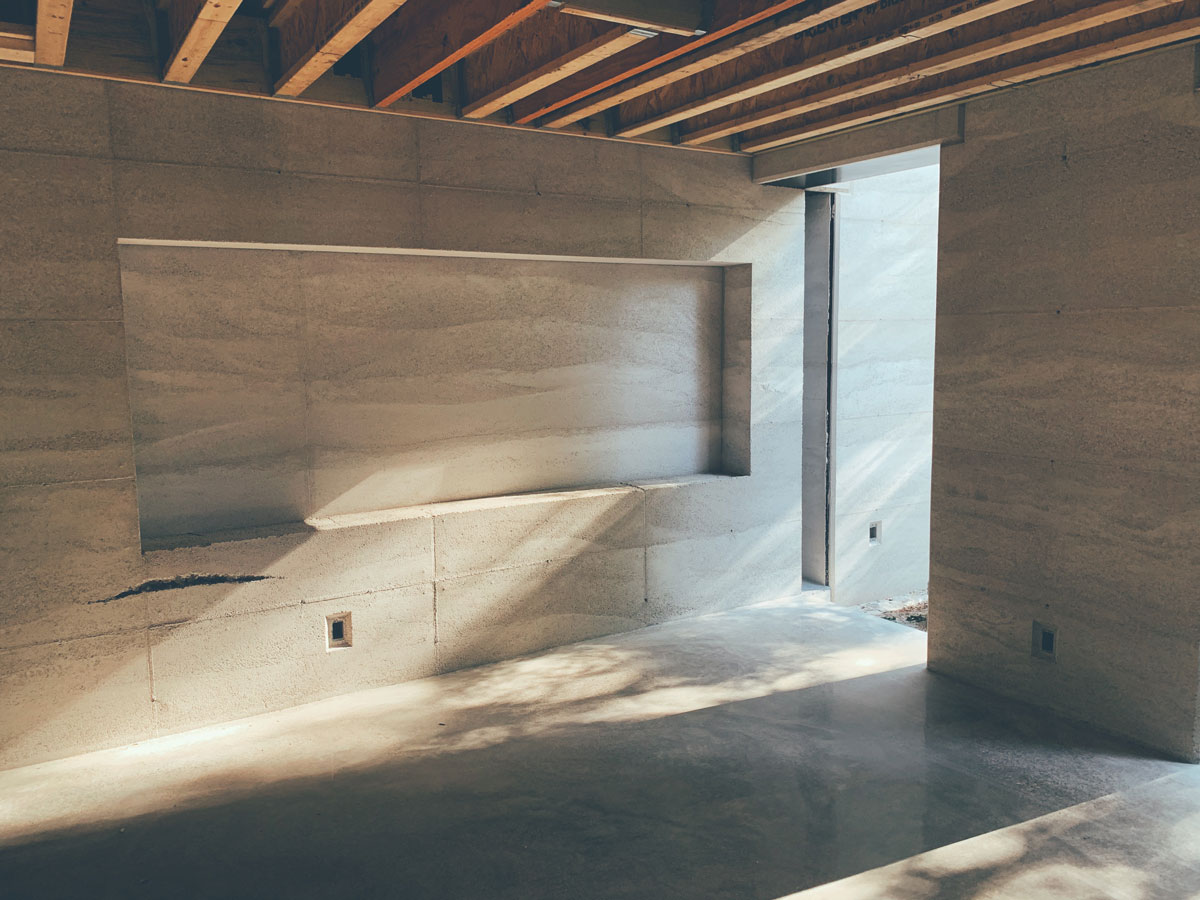 Late afternoon sun reflecting off the polished concrete terrazzo floor on the rammed earth wall