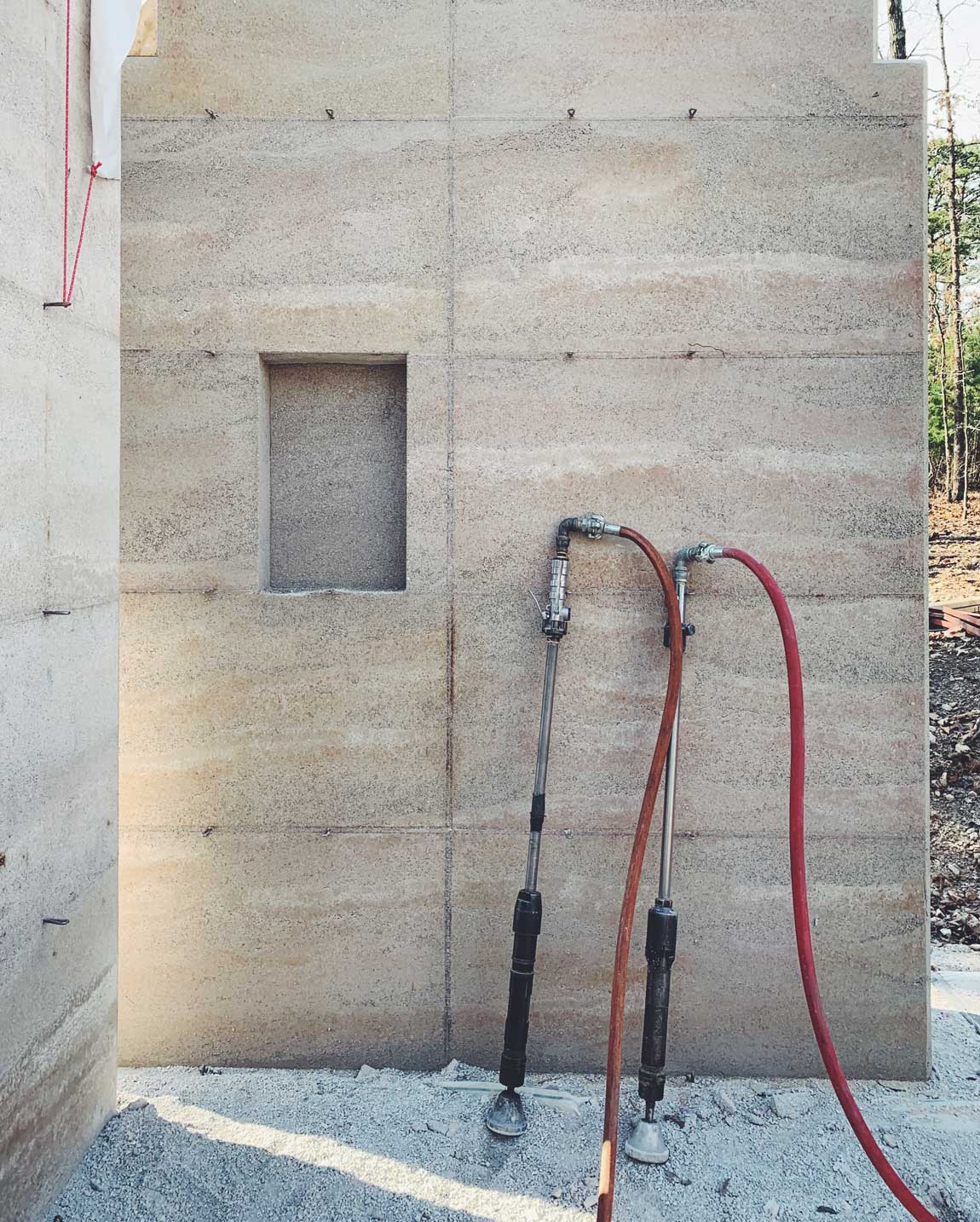 2 rammers against a rammed earth wall - the quality of light and texture is amazing