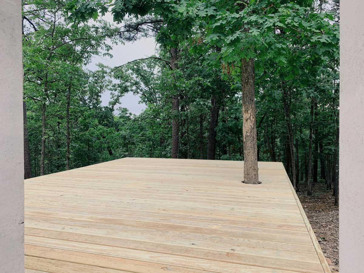 The finished modern wood deck with the oak tree growing through it.