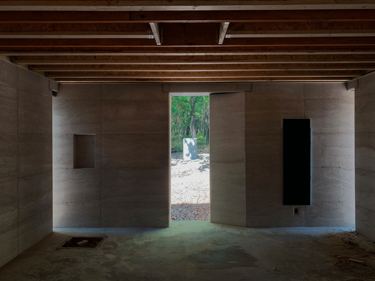 light and shadow dancing on rammed earth walls in a modern custom home