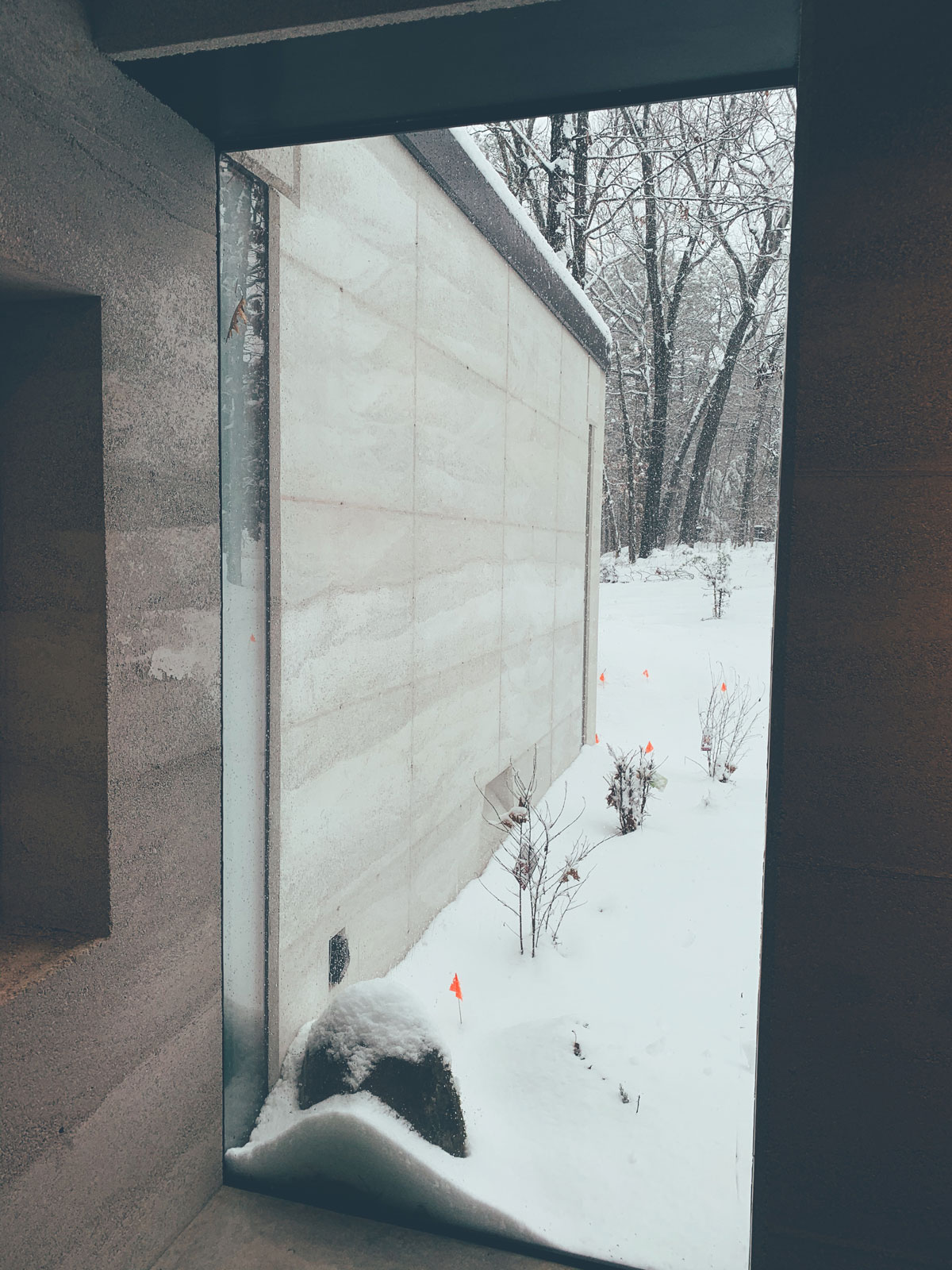 Snow built up against the glass at the modern cabin